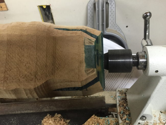 He mounted the wood on his lathe and started rounding the corners.