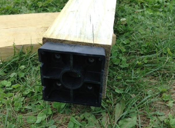 By adding plastic standoffs to the bottom of each post, he ensured that the wood would not come into direct contact with concrete. That'd prevent it from rotting.