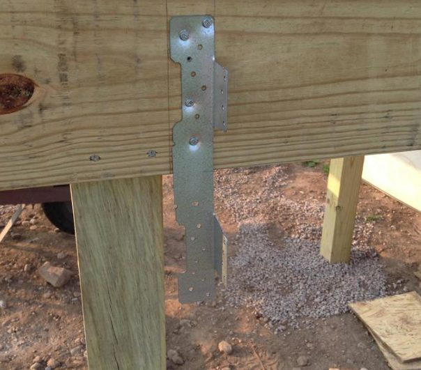 Once the frame was in place, he determined where the steps for the deck would go before mounting some stair stringer brackets.