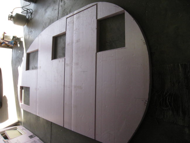 He began constructing the walls, making sure to cut out space for the door and windows.