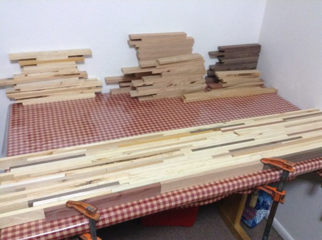 After sawing the wood into smaller strips and stacking them, he began laying out the tabletop.