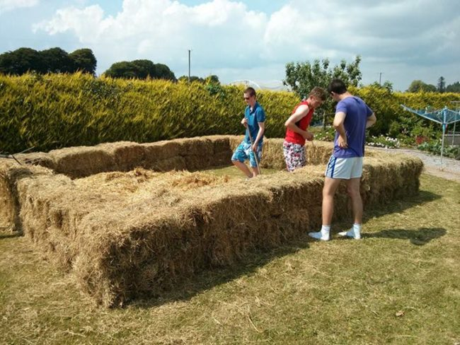 They began stacking bales of hay in the shape of their pool.