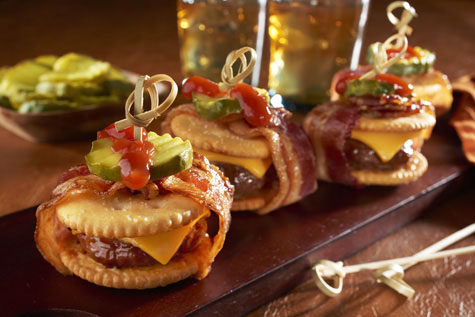 "Cut down on the carbs with these <a href=""http://www.snackworks.com/recipe/bacon-wrapped-cheeseburger-ritzwich-187016.aspx"" target=""_blank"">mini cheeseburger sliders</a>."