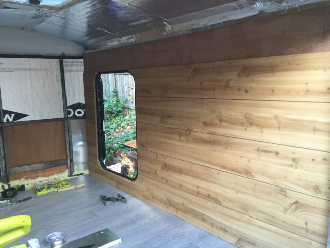 Hookhands began installing faux wood paneling on the walls of the camper.