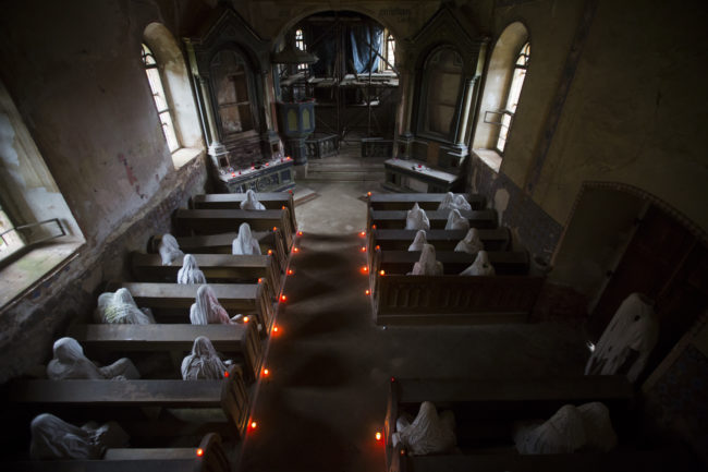 """Inside is a completely different story. The pews are lined with hooded """"ghosts"""" that represent the Sudeten Germans who used to live in the area."""
