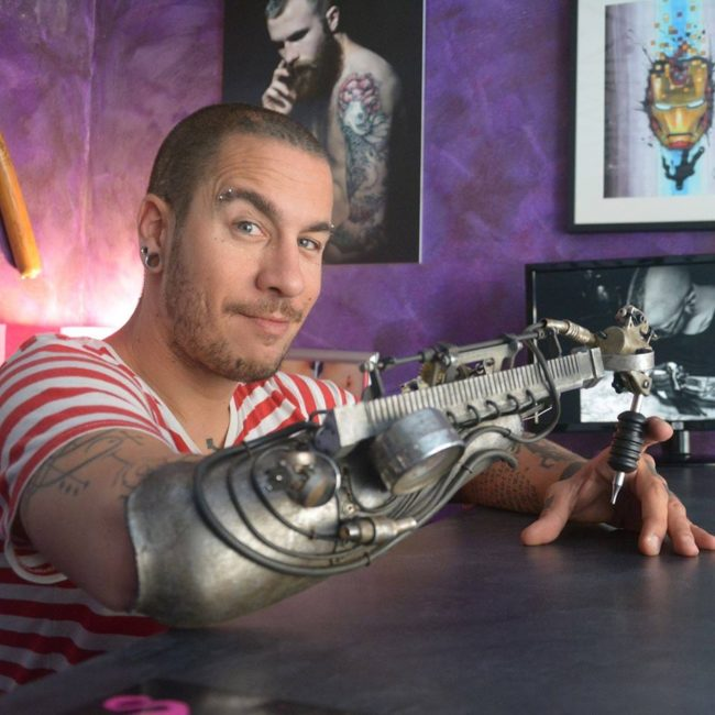 Gonzal decided to mount a tattoo machine onto an existing prosthetic arm and give it to Tenet.  He also added parts from a mechanical typewriter and a gramophone, then painted it for a rusty appearance.