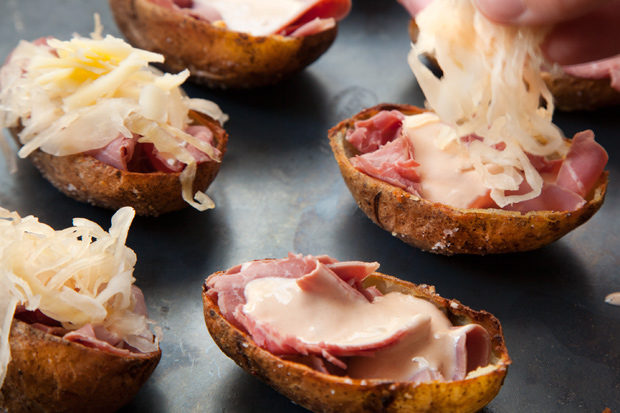 """Making Reuben sandwiches for an entire party would be near impossible, but <a href=""""http://www.chowhound.com/recipes/reuben-potato-skins-29408"""" target=""""_blank"""">Reuben potato skins</a>? That's totally doable!"""