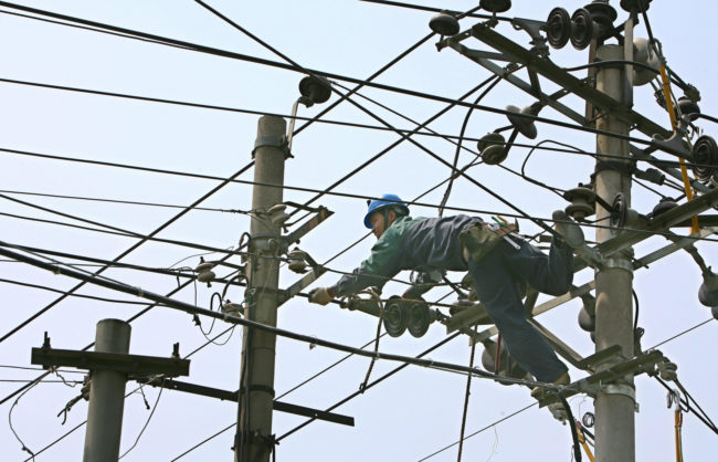 Electricians working on high voltage wires in China