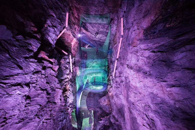 Giant net trampolines are suspended above the cave floor with neon lights brightening up the space.